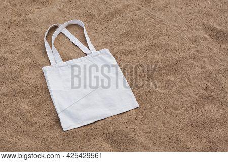 White Cotton Or Mesh Bag On Beach Sand Background. Zero Waste, No Plastic, Eco Friendly Shopping, Re