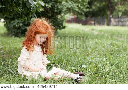 A Smiling Red-haired Little Girl With Loose Curly Long Hair In A Dress Walks In A City Park And Look