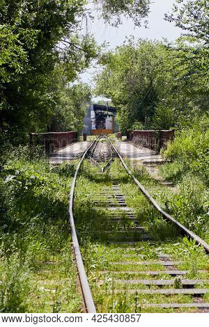Railway Track Overgrown With Grass Directed To The Factory Gate. Railway Dead End
