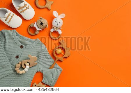 Flat Lay Composition With Baby Clothes And Accessories On Orange Background, Space For Text