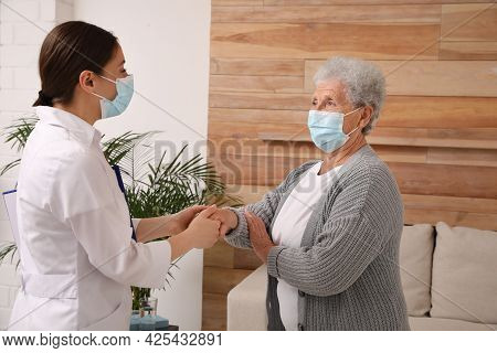 Doctor Taking Care Of Senior Woman With Protective Mask At Nursing Home
