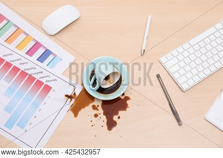 Cup With Saucer And Coffee Spill On Wooden Office Desk, Flat Lay