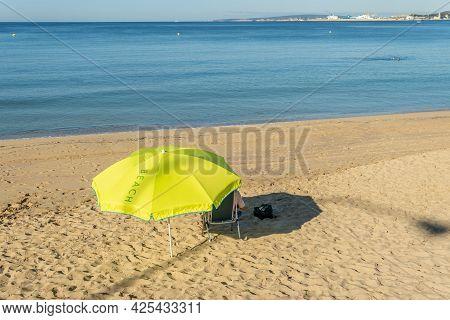 Unrecognizable Person Under A Yellow Umbrella On A Beach On The Island Of Mallorca At Sunrise