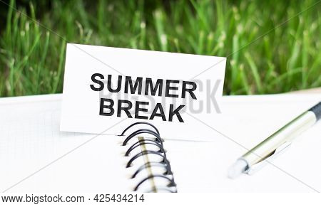 Text Summer Break On A White Card, Which Lies On A Blank Notebook With A Pen On A Green Background.