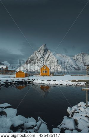 Yellow cabins by a snow lakeside