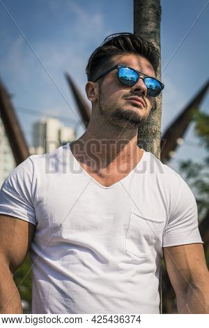 Man In Urban Setting In Front Of Big Metal Structure
