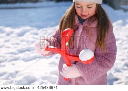 Cute Little Girl Playing With Snowball Maker Outdoors