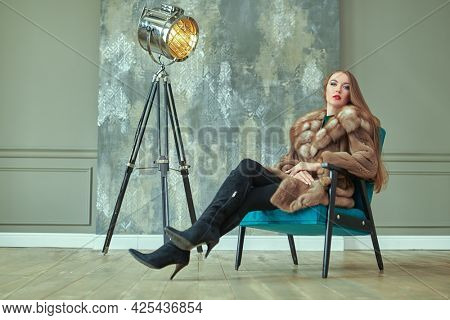 Fur coat fashion. Beautiful glamorous woman in an expensive mink and sable fur coat poses in luxury apartments. Full length portrait.