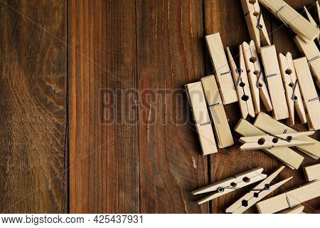 Pile Of Clothespins On Wooden Table, Flat Lay. Space For Text