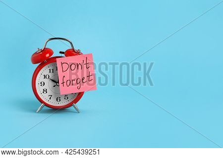 Alarm Clock And Reminder Note With Phrase Don't Forget On Light Blue Background, Space For Text