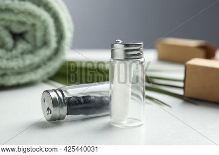 Biodegradable Dental Flosses In Glass Jars On White Table