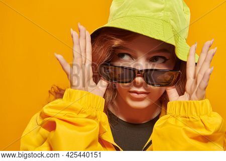 Stylish teenage girl in yellow hoodie and sunglasses poses at studio on a yellow background. Youth style. Modern hip-hop dancer.