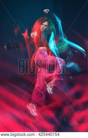 Contemporary dances. Professional hip-hop dancer girl dancing at studio in neon light. Motion.
