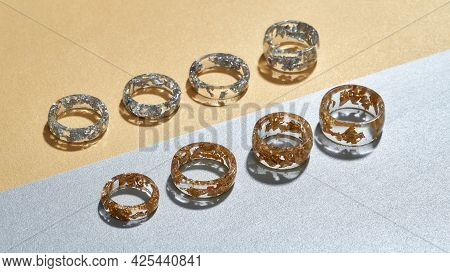 Clear Acrylic Rings With Golden And Silver Filling Lying In Row On Gray Orange Background, Widescree
