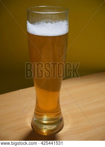 Beer Glass On A Wooden Table. Craft Beer Festival. Beer With Foam In A Pub. Alcohol Drink, Closeup