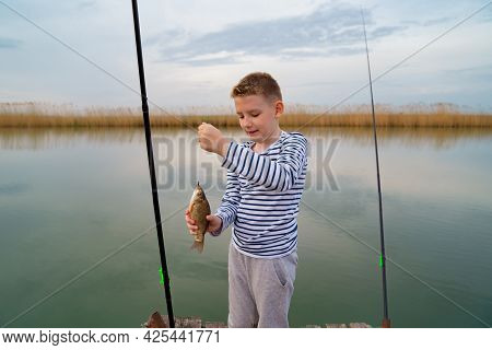 A Boy Catches A Fish On Fishing Rod. Mens Hobby.