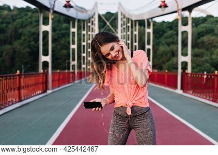 Slim Romantic Girl Listening Music Before Marathon. Outdoor Portrait Of Blithesome Woman Preparing F