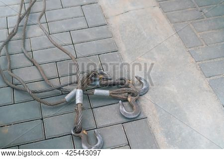 Four Hooks With Steel Cables Lie On The Sidewalk With Copy Space