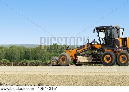 An Orange Grader Is Busy With Road Repairs. Excavator For Road Works. Road Machinery Works Against T