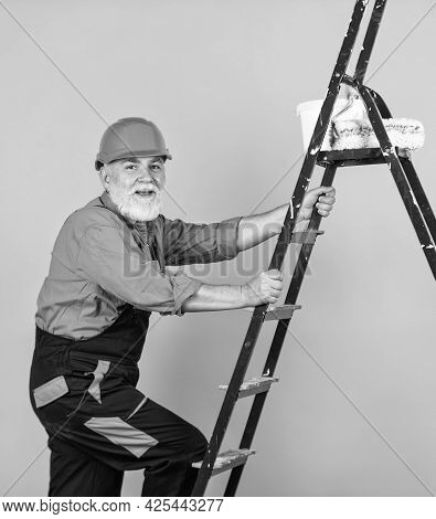 Painter Man Staircase. To Make Repairs. Man In Working Clothes Painting Wall In Empty Room. Painter