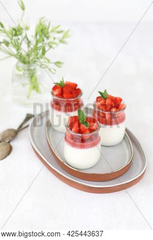 Italian Dessert Panna Cotta With Fruit Jelly And Fresh Pieces Of Strawberries On White Background. C