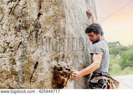 Young Caucasian Man With Beard And Gesture Of Effort Performing Rock Climbing. Person Doing Physical