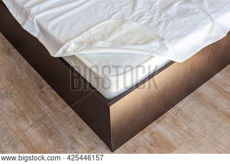 Corner Of A Wooden Bed With A High Mattress And A Protective Cover. Putting On The Mattress Topper.