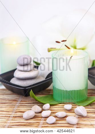 Image of pebble stones in black plate, white lily flower, fresh green leaves, candle on bamboo table in spa salon, natural cosmetics, relaxation in dayspa, meditation and harmony concept