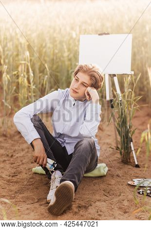 A Young Handsome Fellow Artist Sits Wistfully Near An Easel With A Canvas In Nature