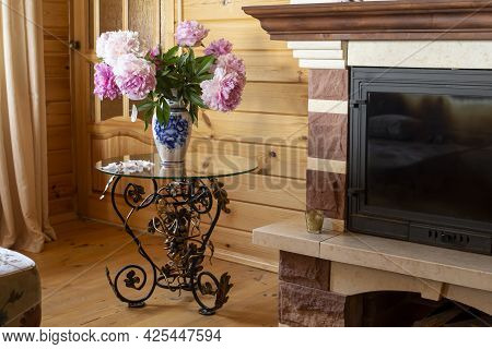 A Beautiful Wrought-iron Table With A Vase Of Flowers In The Living Room Near The Fireplace. Cozy In