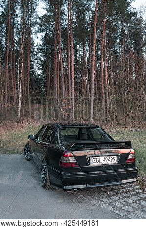 Goleniow, Poland - April 20th, 2021: Old Black Tuned Mercedes Benz C-class (w202 Model) Near Forest.