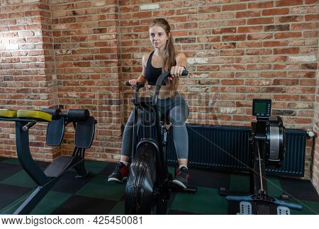 Attractive Woman Using Exercise Bike At Gym. Fitness Female Using Air Bike For Cardio Workout At Fit