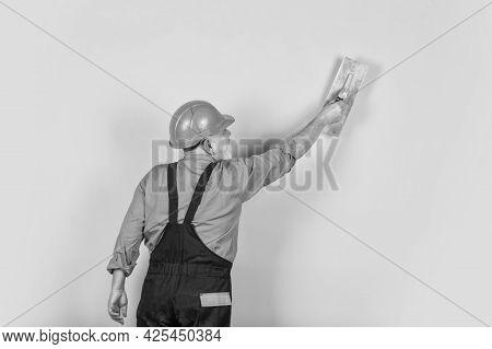 Plaster Trowel Spatula On Yellow Drywall Plasterboard. Plasterer In Working Uniform Plastering Wall