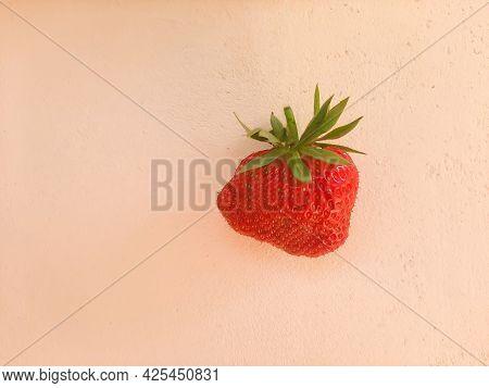 Ugly Red Ripe Deformed Strawberry On A Beige Concrete Background. Funny, Unnormal Vegetable Fruit Or