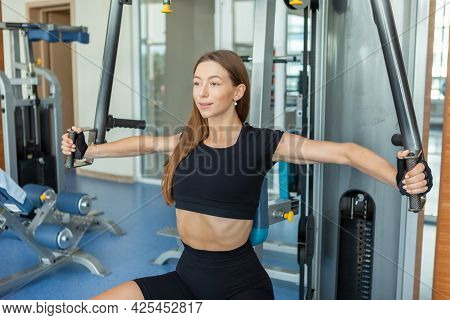 Young Fit Woman Working Out At The Gym On Peck Deck Machine. Chest And Shoulders Workout