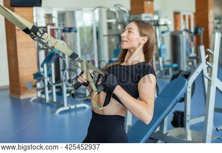 Beautiful Muscular Woman Doing Exercise With Suspension Strap System In Gym