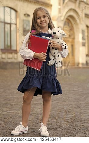 Learning And Fun For Everyone. Happy Kid Hold Books And Toy. Back To School Supplies. School Uniform