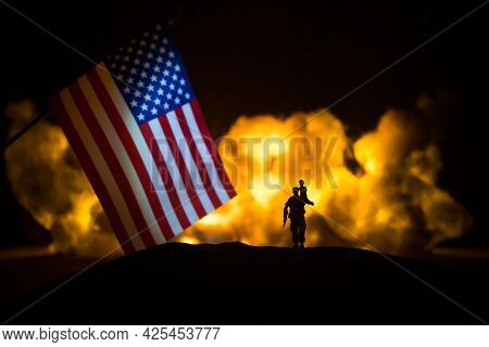 Us Small Flag On Burning Dark Background. Concept Of Crisis Of War And Political Conflicts Between N