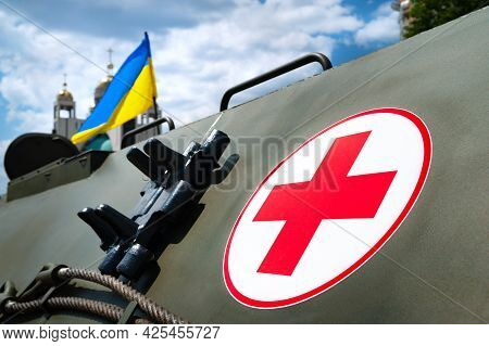 Medical Armored Personnel Carrier. Medical Cross On The Armor Of An Armored Vehicle Against The Back