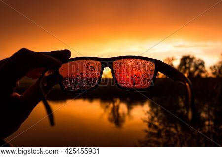 Sunglasses In Water Drops During Colorful Sunset