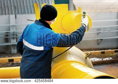 A Painter In Working Clothes Paints A Metal Shut-off Valve For Gasification From A Compressor Gun On
