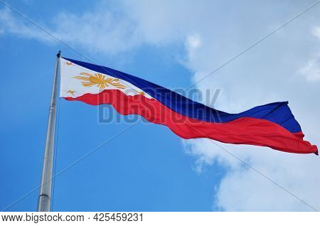 Flag Of Philippine Or Filipino Nation On Steel Pole At Outdoor In Garden With Sky Clouds Background