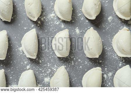 Concept Of Cooking Vareniki Or Pierogi On Gray Background
