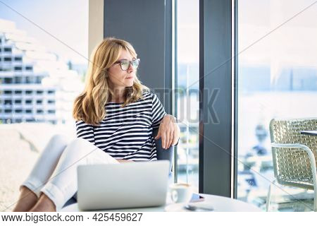 Smiling Mature Woman Sitting On Chair And Looking Thoughtfully While Looking Out The Window At Home.