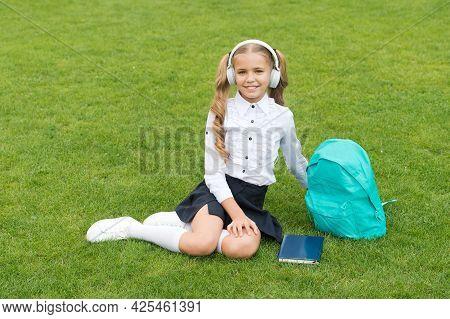 Happy Schoolchild In Uniform Listen To Music In Headphones Sitting On Green Grass, School Holidays