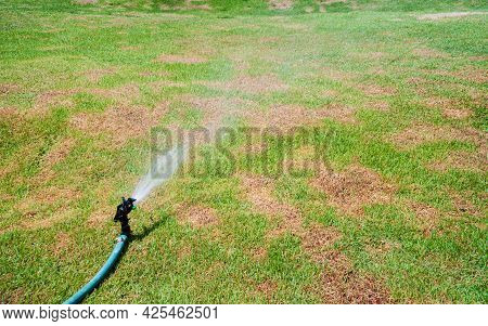 Lawn Irrigation System On A Green Lawn. Spraying Clean Water Stream Plastic Sprinkler On The Grass L
