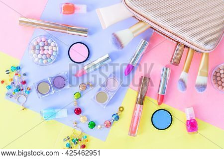 Colorful Scattered Make Up Products With Golden Pursue Close Up On Plain Color Block Background