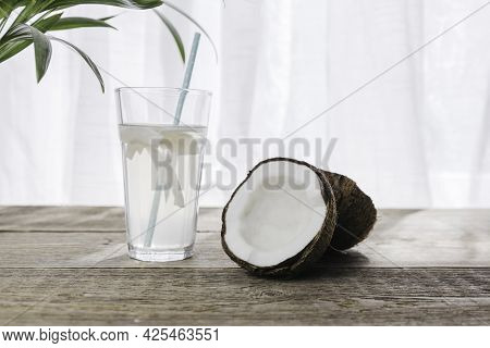 Coconut Water In A Glass On A Wooden Table With An Open Coconut With White Pulp. An Organic Healthy