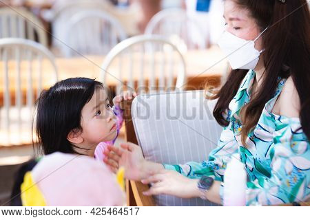 Asian Mother Is Applying Sunscreen To Her Daughter Before Going Into The Sea. To Protect Your Skin F