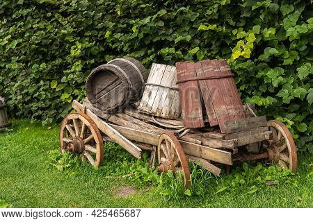 Old Traditional Wooden Tip Cart With Large Broken Barrels Stands On Lush Green Lawn Near High Plant